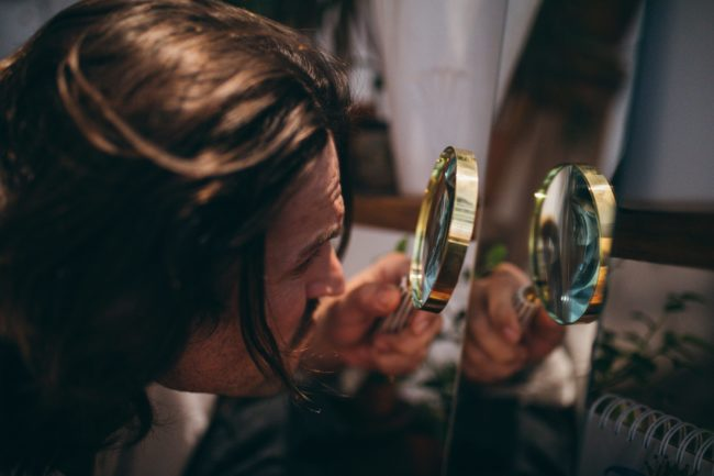 a man using magnifying glass to analyse